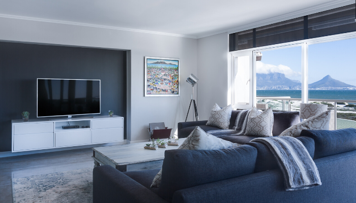 A blue and white themed living room with a view of the ocean.