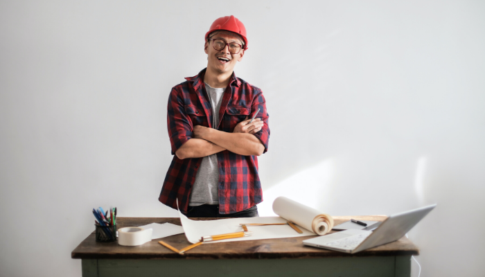 A contractor with a red helmet and a plaid shirt crossing his arms and smiling with construction plans and supplies in front of him.