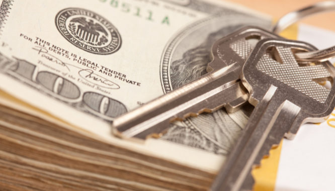 A key on top of a stack of hundred-dollar bills symbolizes an all cash offer