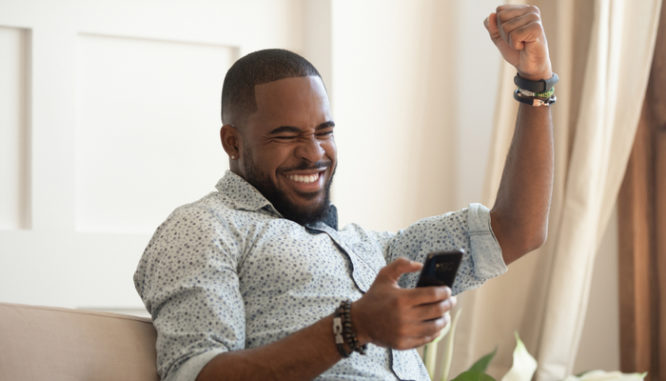 A happy Black man with a short beard looking at his phone and raising one arm in victory because his all cash offer was accepted