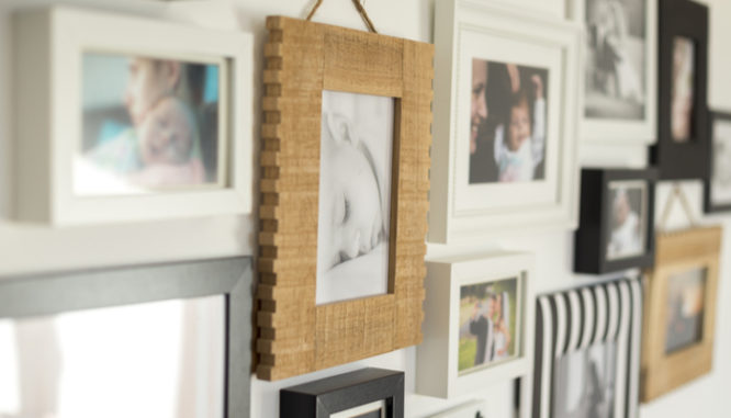 Family portraits on a gallery wall are one way to arrange wall art in a new house