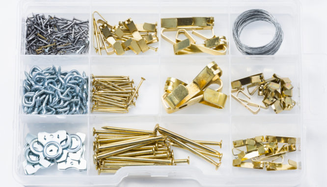 Hooks, nails, wire, and other tools for arranging wall art in a new house in a clear plastic container