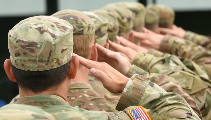 A row of men in military uniforms saluting; veterans can buy a house without having to pay PMI