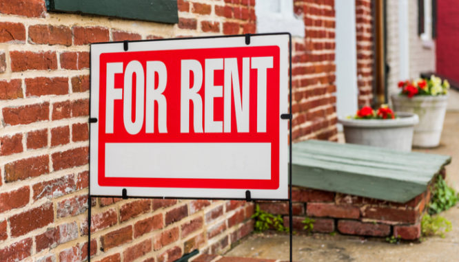 A for rent sign outside of a brick apartment building shows how to invest 5000 dollars in real estate