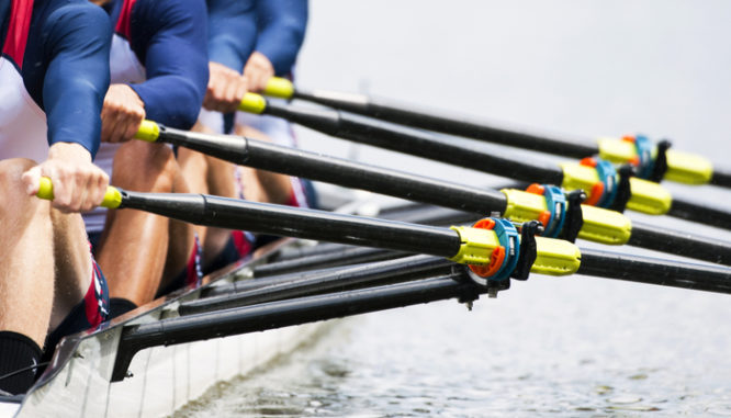 A close up of a team of rowers' oars showing how to invest 5000 dollars in real estate: partner up