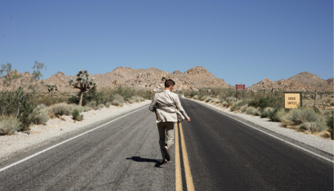 A man in a gray suit running down a desert highway, in order to go live off the grid.