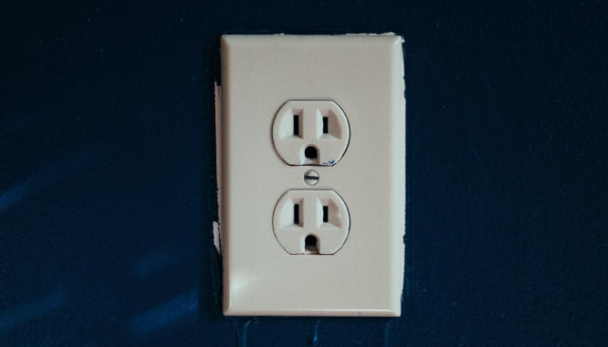 A photo of an electrical outlet illustrates the topic of common repairs needed after.a home inspection.