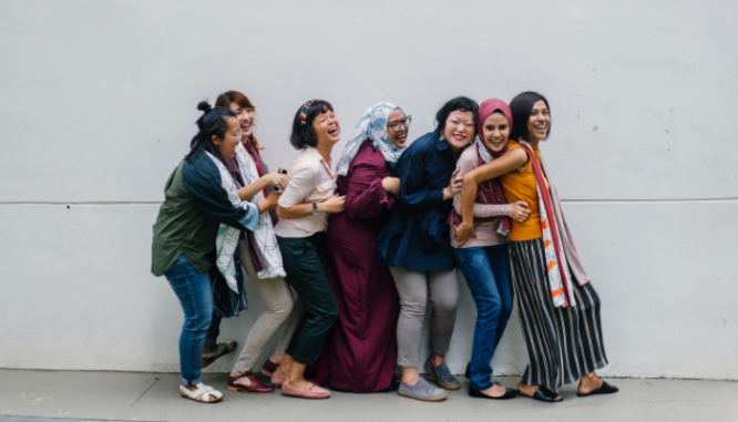 A line of women from varying ethnicities and wearing different outfits from jeans to head veils are smiling and looking forward to working against interlocking oppressions in real estate.