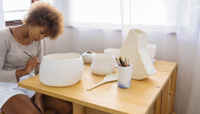 A Black woman with a natural afro wearing shorts and sitting a table at home, painting her pottery.