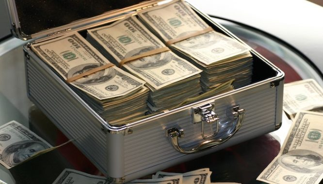 A chrome suitcase filled with $100 bills illustrates the money lost through real estate appraisals and racism or bias