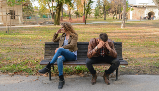 A man and woman sitting on a park bench, the man has his head in his hands and the woman is looking away, frustrated.